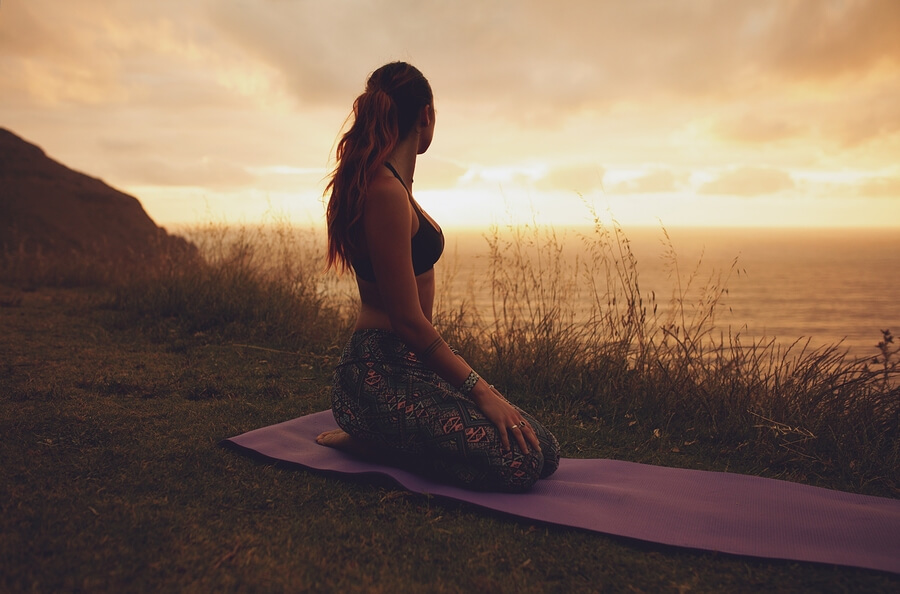 Woman on yoga mat watching sun rise near Cronulla